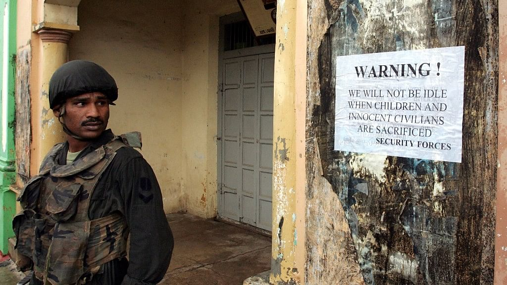 A Sri Lankan soldier stands by an army poster on the streets of Jaffna,   northern Sri Lanka, 5 January 2006. (Photo: Reuters)