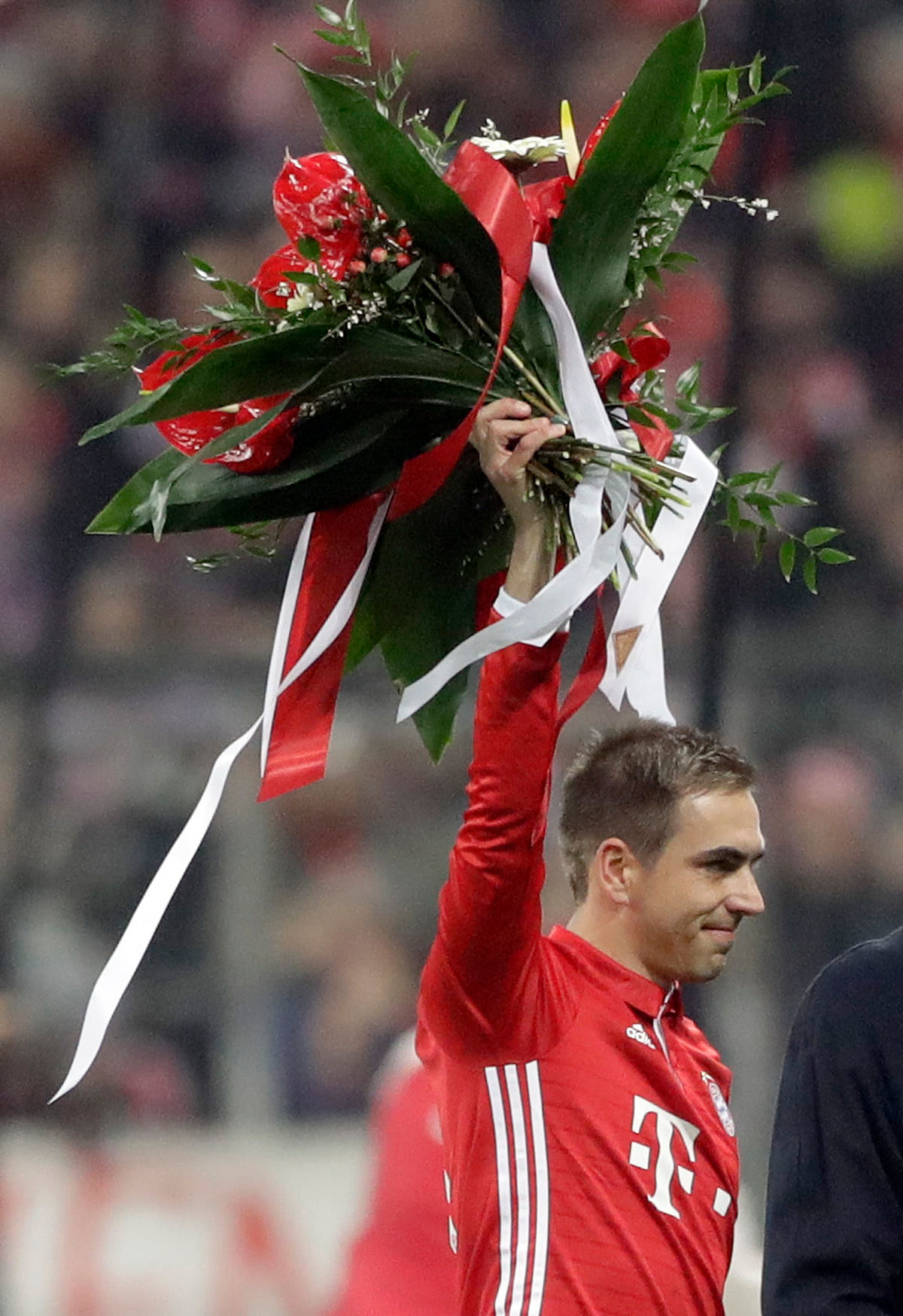 Bayern's Philipp Lahm waves on the field with flowers prior to the German Soccer Cup match between FC Bayern Munich and VfL Wolfsburg at the Allianz Arena stadium in Munich. (Photo: AP)