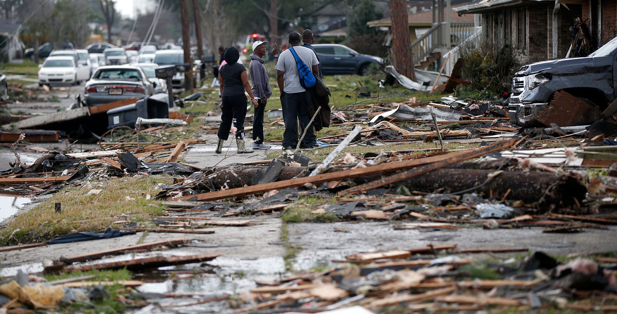 People walk amongst debris from destroyed homes after a tornado tore through the eastern neighbourhood in New Orleans. (Photo: AP)