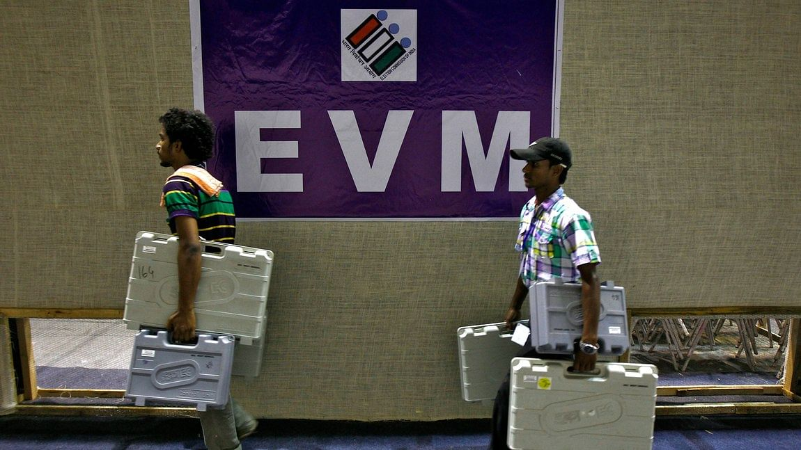 Election staff carry electronic voting machines (EVM) after collecting them from a distribution centre.