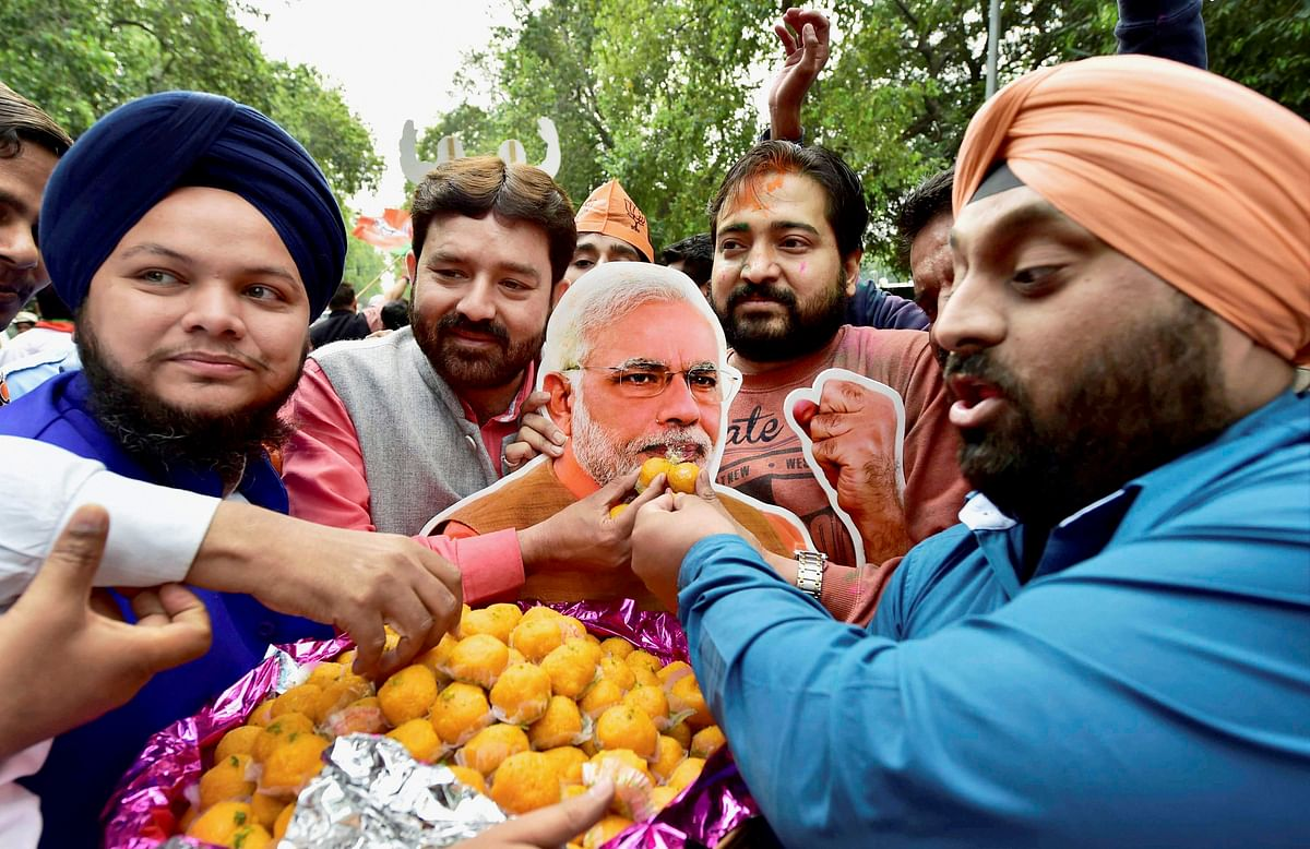 BJP supporters offer sweets to a cutout of PM Narendra Modi as they celebrate the party's victory in the assembly elections. (Photo: PTI)