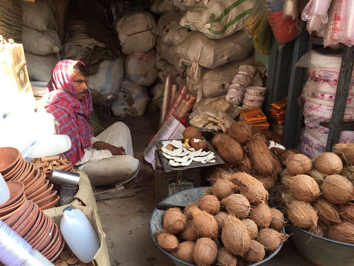 A coconut seller reading religious texts. (Photo: Jyoti Malhotra)