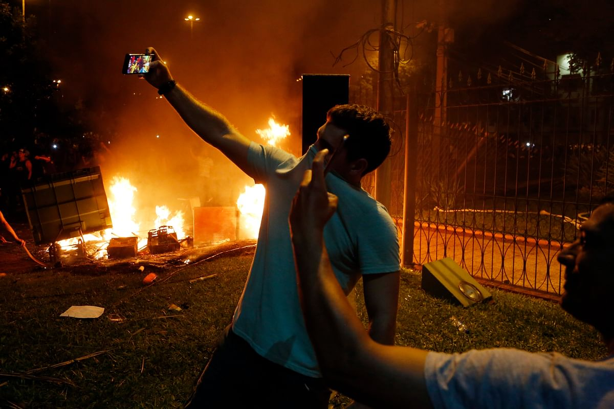 "Two men pose for ""selfies"" during the protest against presidential re-elections at Congress in Asuncion. The protesters set ablaze the first floor of the Congress. (Photo: AP)"