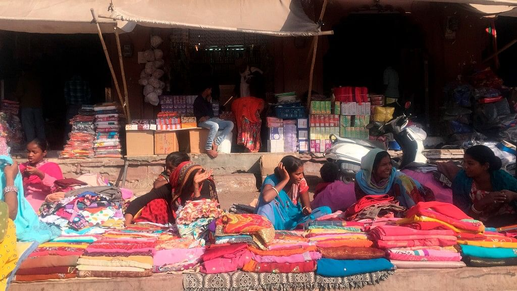 Women sell brightly coloured textiles in Jodhpur. India's colorful and complex culture was highlighted in a month-long cross-country trip by an American woman traveling solo, who found she was sometimes as much an object of curiosity to locals as they were to her. (Kristi Eaton via AP)<a></a>