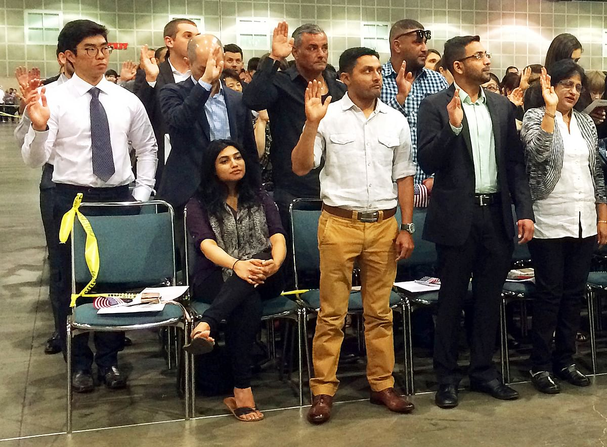 Indian-born U.S. national cricket team player Timil Kaushik Patel, second from left, takes an oath as a naturalized U.S. citizen at a ceremony in Los Angeles, Tuesday, April 18, 2017. His wife Pooja Patel is seated, left. (Photo: AP)