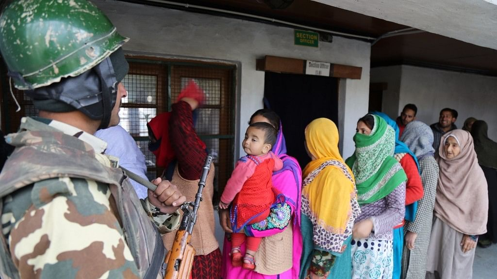A soldier stands guard as women queue up to cast their votes during byelection for the Srinagar-Budgam parliamentary seat in Srinagar on 9 April 2017. (Photo: IANS)