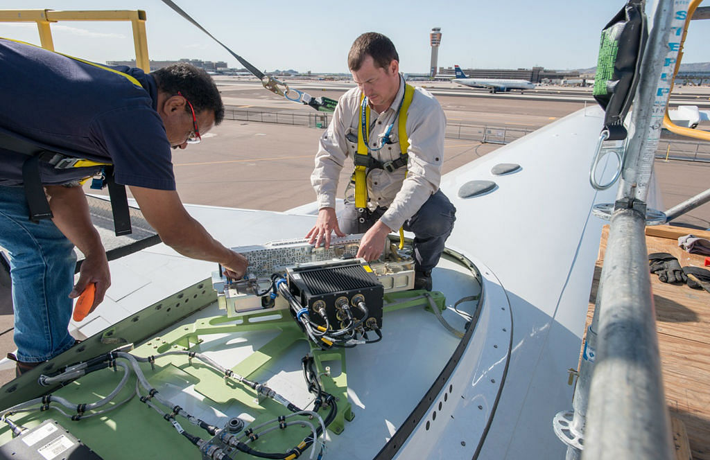 Engineers fitting in-flight Wi-Fi router on a test Boeing B757 plane. (Photo Courtesy: Honeywell Aerospace)