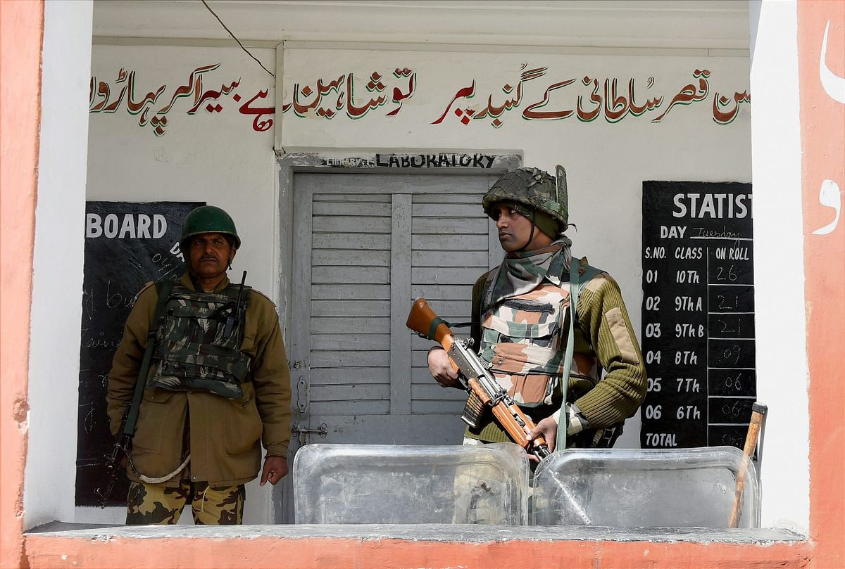 A jawan stand guard outside a polling station for Srinagar Parliamentary constituency of Jammu and Kashmir at Budgam in Srinagar on Sunday. (Photo: PTI)