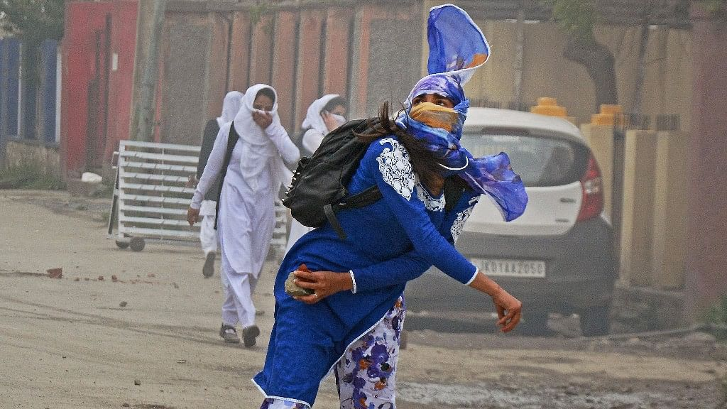 A girl student pelts a stone at security personnel during clashes in the vicinity of Lal Chowk in Srinagar. (Photo: PTI)