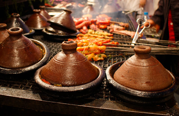 Tagines being prepared over charcoal fire. (Photo: iStock)