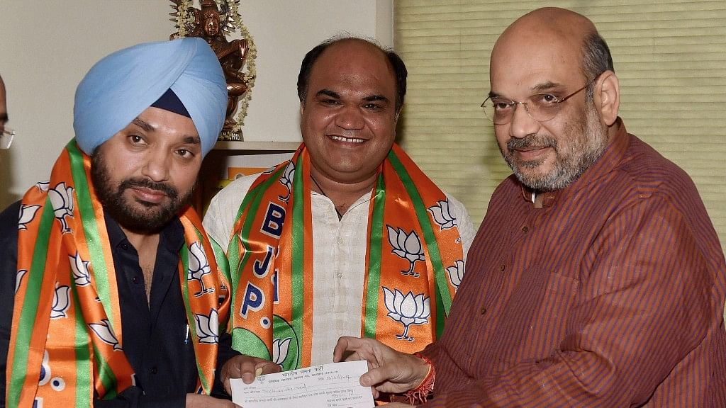 BJP President Amit Shah presents the party membership slip to former DPCC President Arvinder Singh Lovely as he joins Bharatiya Janata Party