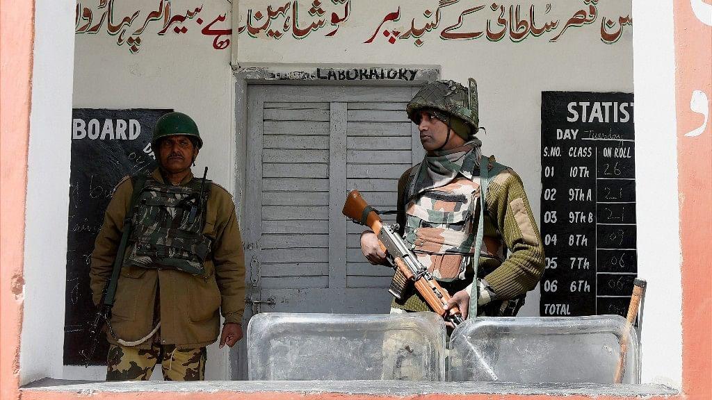 Jawans stand guard outside a polling station for Srinagar Lok Sabha seat in Budgam on Sunday. (Photo: PTI)