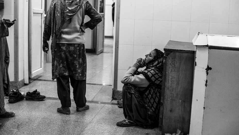 A woman waits outside an operation theatre for her injured son, who received pellet injuries during a protest in Budgam district of Kashmir. (Photo: Hashim Hakeem)