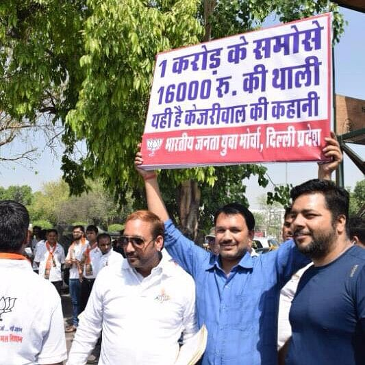 """BJP volunteers hold placards criticising Kejriwal govt for spending Rs 1 crore on snacks, as revealed in an RTI query. (Photo Courtesy: <a href=""""https://www.facebook.com/pg/BJP4Delhi/photos/?ref=page_internal"""">BJP Delhi</a>/ Facebook)"""