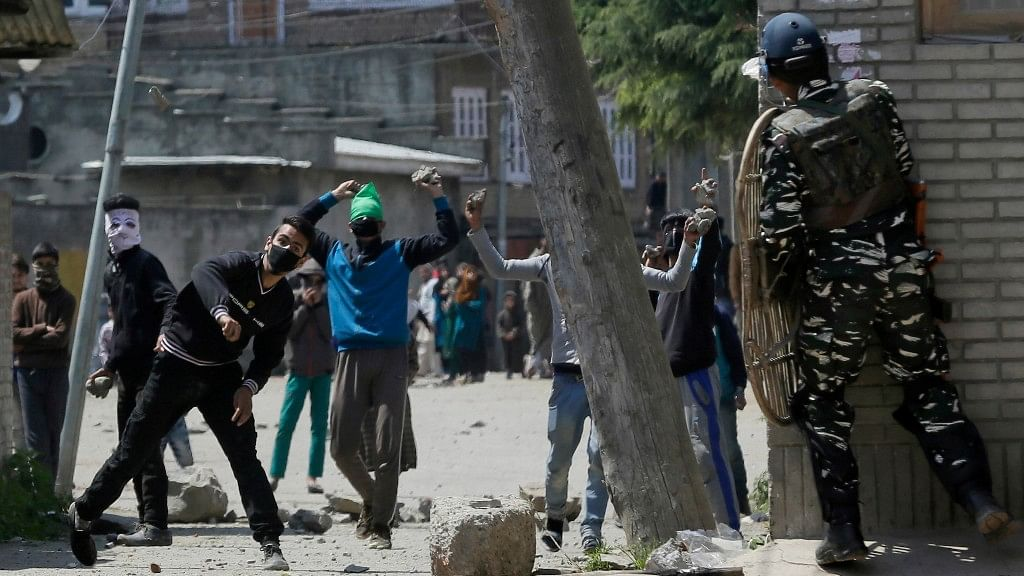 Kashmiri protesters throw stones on Indian security men outside a poling station during a by-election to an Indian Parliament seat in Srinagar, Kashmir. (Photo: AP)