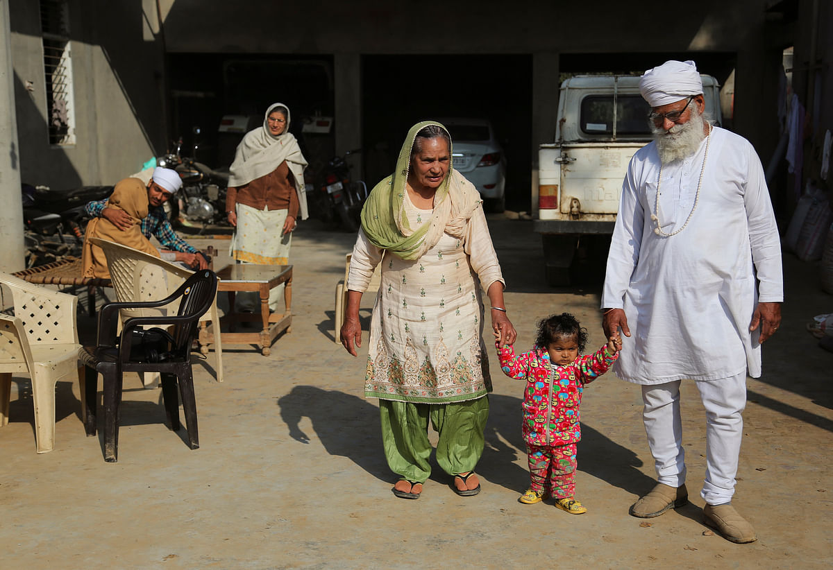 Manjeet Kaur, left, and her husband Gurdev Singh, right, walk with their daughter Gurjeet Kaur in the compound of their house in Ellenabad. (Photo: AP)