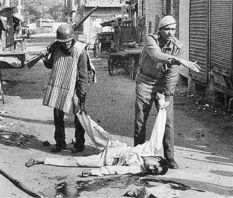 "Policemen drag the body of a victim during the Bombay riots. (Photo courtesy: <a href=""https://www.naukrinama.com/stressbuster/horrifying-real-pictures-of-riots-in-india-which-will-make-you-cry-in-empathy/41/"">Naukrinama.com</a>)&nbsp;"