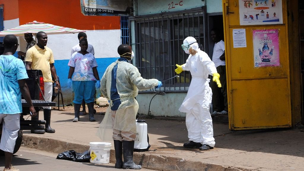 File Photo: Member of a burial team sprays a colleague with chlorine disinfectant in Monrovia, the capital of Liberia 20 October 2014. (Photo: Reuters)