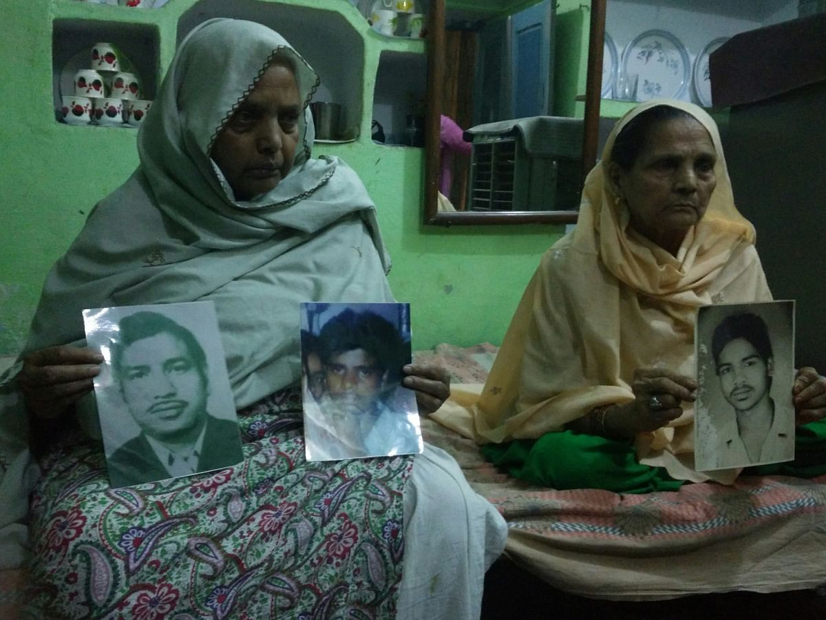 Zareena and Hajra holding pictures of their family members killed in the massacre. (Photo Courtesy: Mahtab Alam)