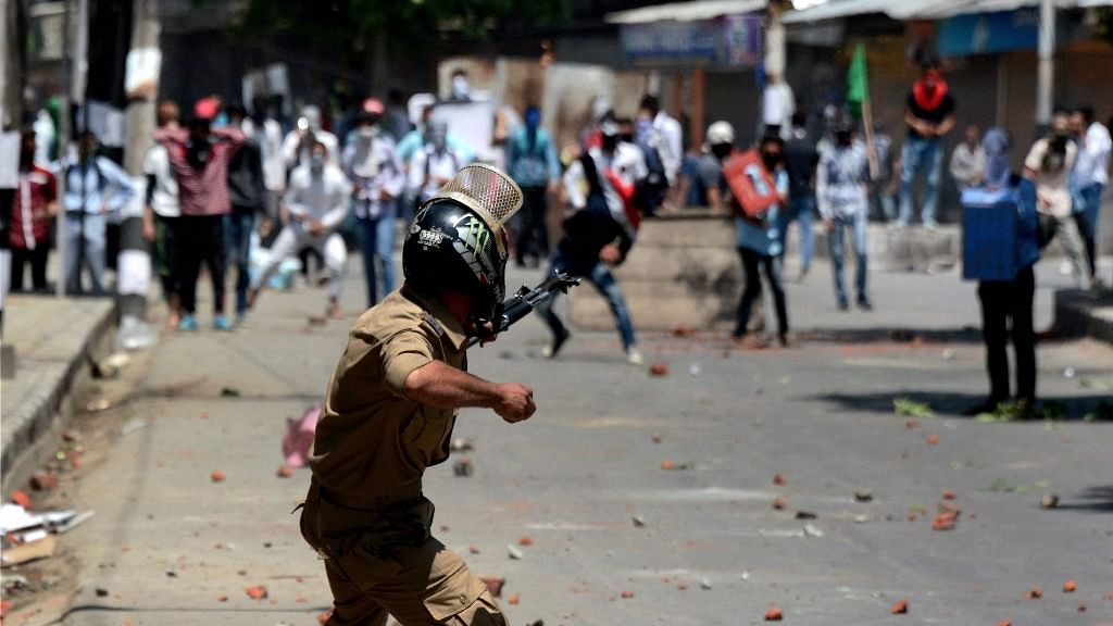 A Policeman in action against stone pelters during violent clashes which erupted following the killing of Slain Hizbul Mujahideen Commander Zakir Ahmad Bhat. (Photo: PTI)
