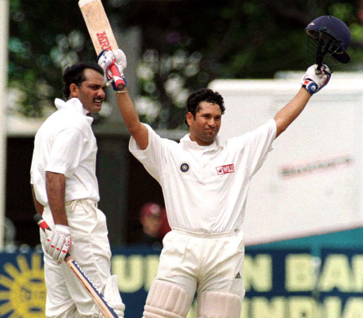 Sachin Tendulkar raises his arms to the crowd after scoring a century against New Zealand as his captain Mohammad Azharuddin looks on, during day four of the second cricket test at the Basin Reserve on 29 December. (Photo: Reuters)