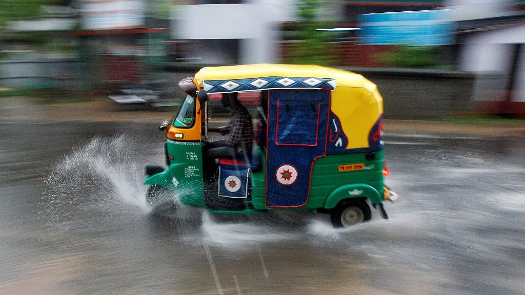 A person drives an auto rickshaw through heavy rains in Agartala,  1 June 2017. (Photo: Reuters/Jayanta Dey)