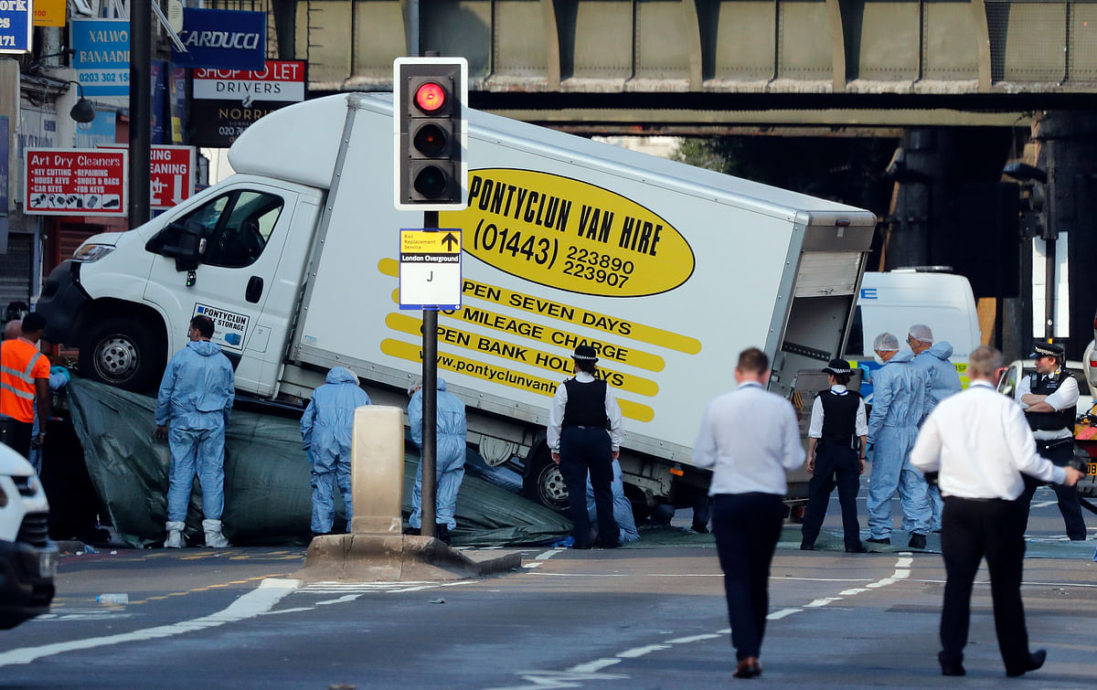 Forensic officers move the van at Finsbury Park in north London, where a vehicle struck pedestrians in north London. (Photo: AP)
