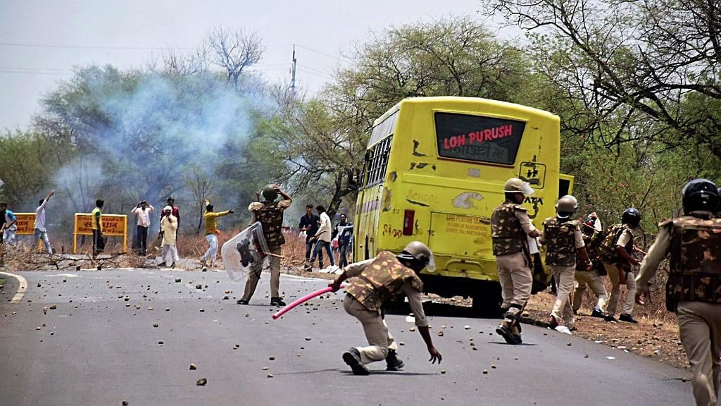 Farmers pelting stones as they clash with the police during their agitation in Phanda near Bhopal on Friday. (Photo: PTI)