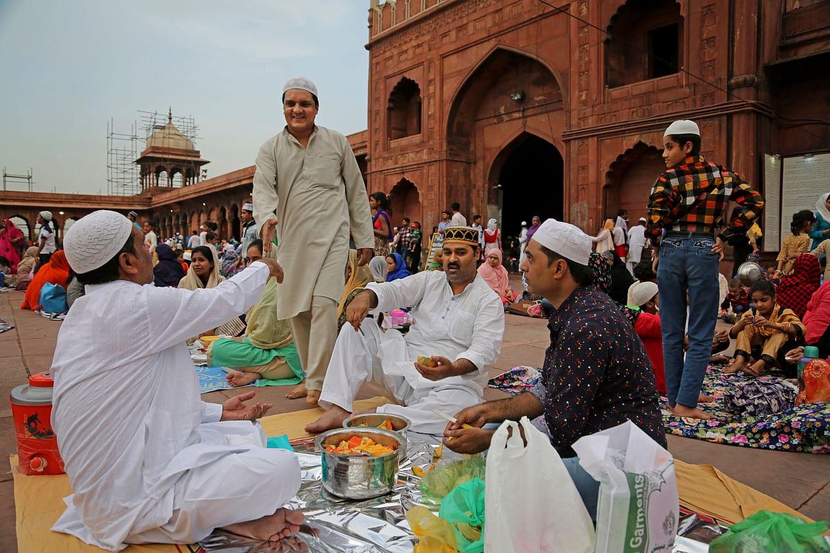 Muslims in Delhi's Jama Masjid distributing sweets.