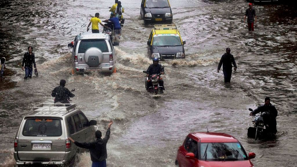 People wade through a water logged road after heavy rains in Mumbai (Photo: PTI)