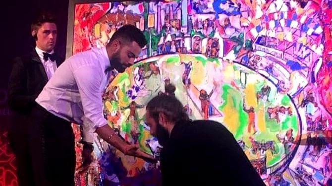Virat Kohli ready to create a hand print on the painting, with artist Sacha Jafri applying paint on his hand.