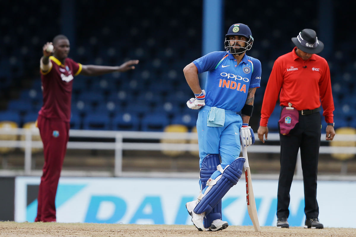 India's captain Virat Kohli stand on his side as West Indies' captain Jason Holder. background, directs his players during their first ODI. (Photo: AP)