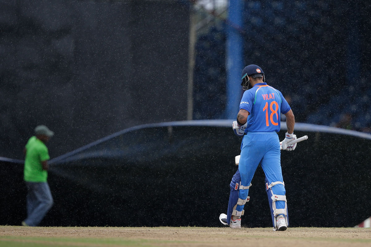 Virat Kohli walks off the field after rain disrupts play during the first ODI against West Indies (Photo: AP)