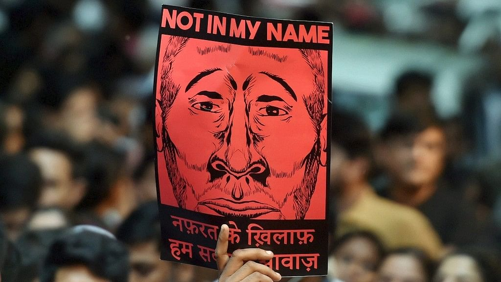 """A protester holds up a """"Not in My Name"""" placard at Jantar Mantar in New Delhi."""