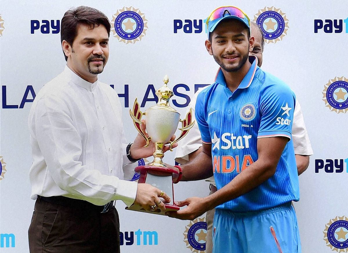 BCCI Secretary Anurag Thakur hands over the winning trophy to India 'A' Skipper Unmukt Chand after they won the 3rd ODI series against Bangladesh 'A' in July 2016. (Photo: PTI)