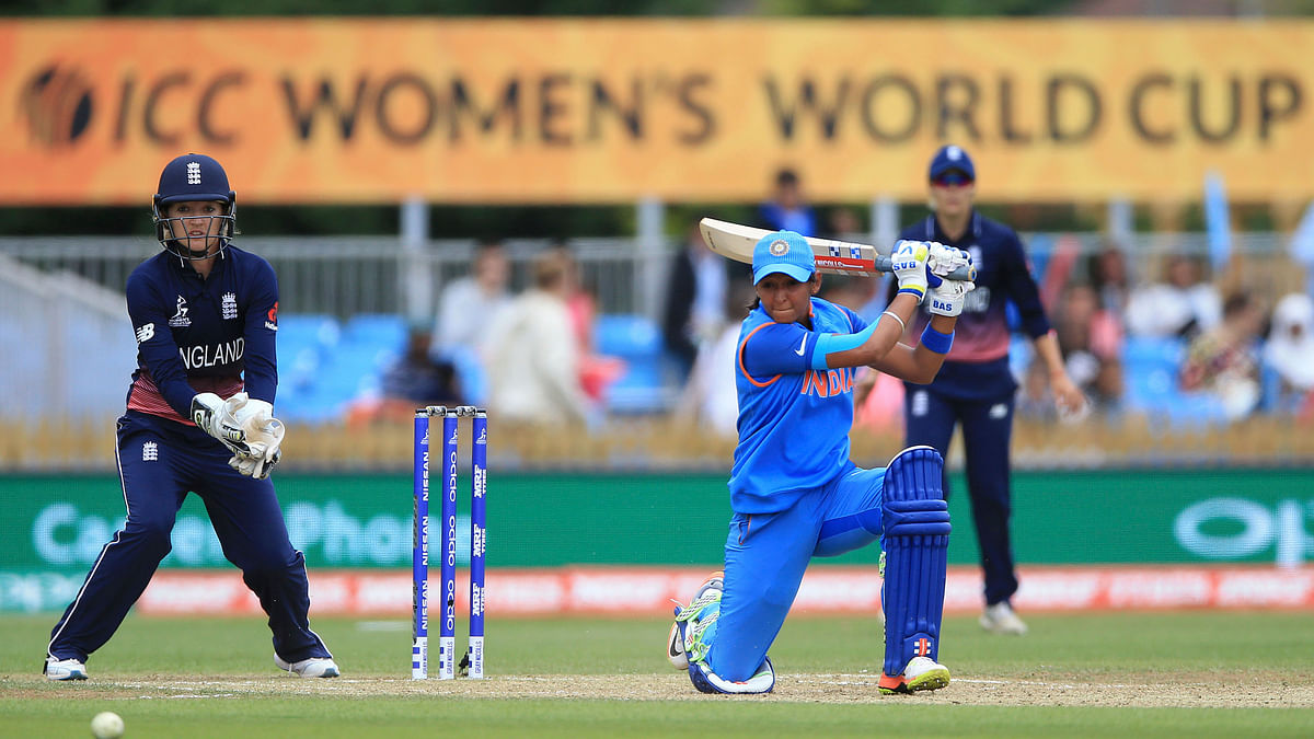 India's Harmanpreet Kaur, right, and England's Sarah Taylor during the ICC Women's World Cup fixture at the County Ground