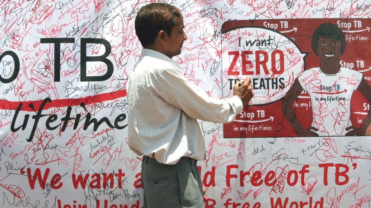 A volunteer signing the signature campaign poster during a TB awareness programme for eradication of TB in India.