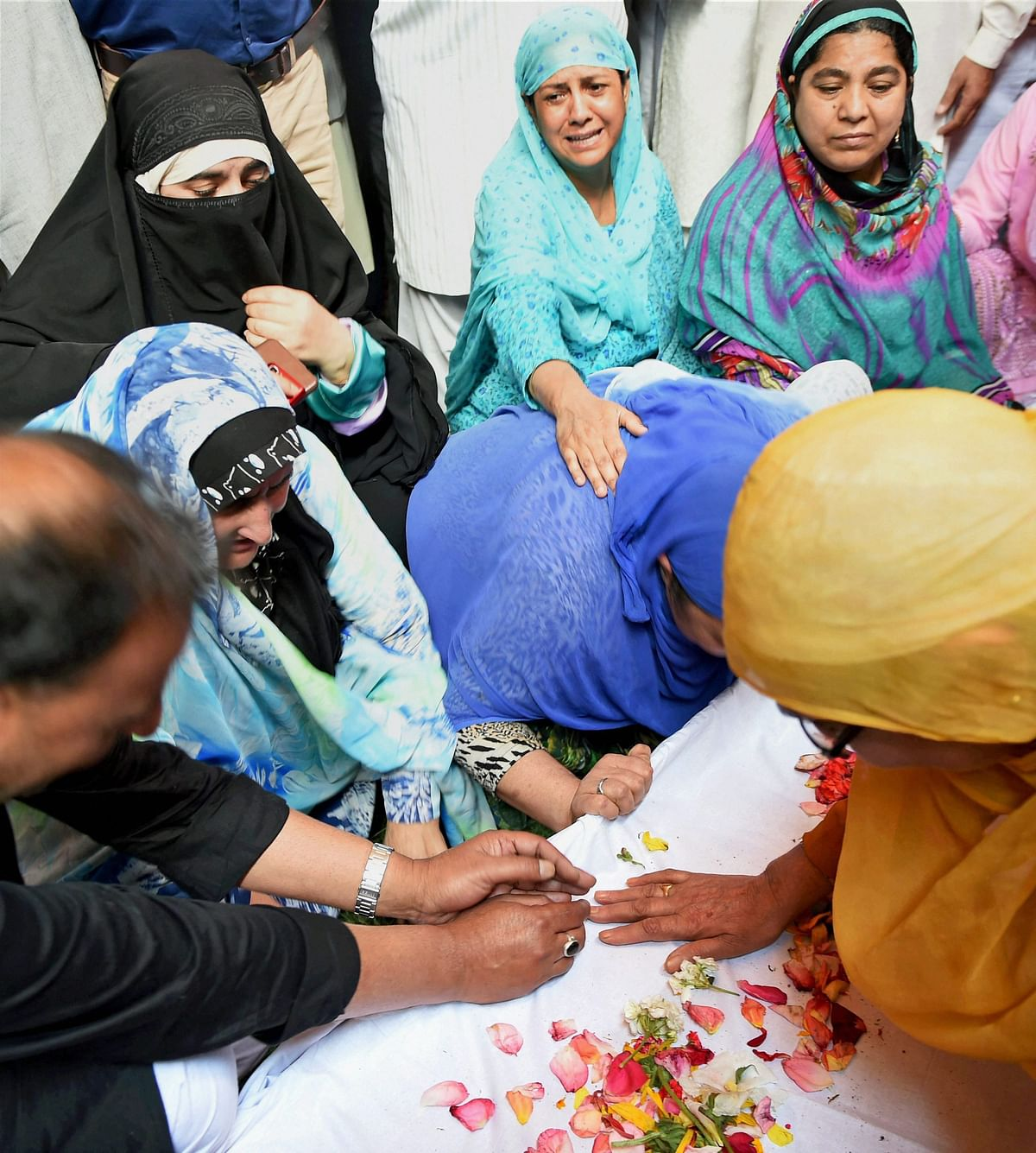 Pandith's family members grieving his death on 23 June, after his funeral ceremony.