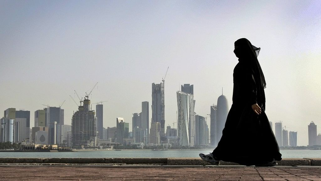 A file image of a Qatari woman walking in front of the city skyline in Doha. (Photo: AP)