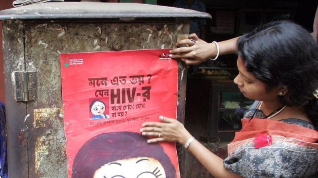 An activist puts up a poster during an AIDS awareness drive in Sonagachi.