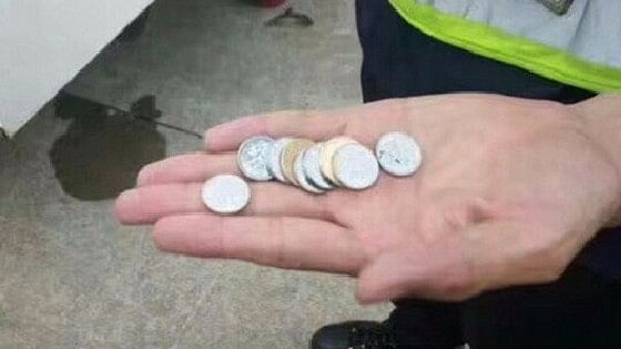 Chinese Police shows the coins retrieved from the plane engine