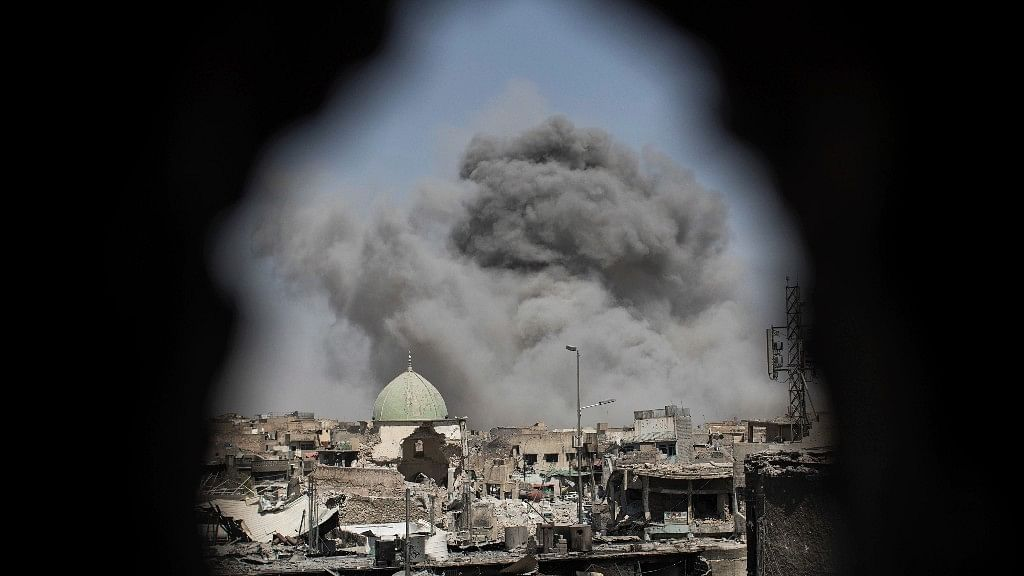 A bomb explodes behind the al-Nuri mosque complex, as seen through a hole in the wall of a house, as Iraqi Special Forces move toward ISIS militant positions in the Old City of Mosul, Iraq, Thursday.