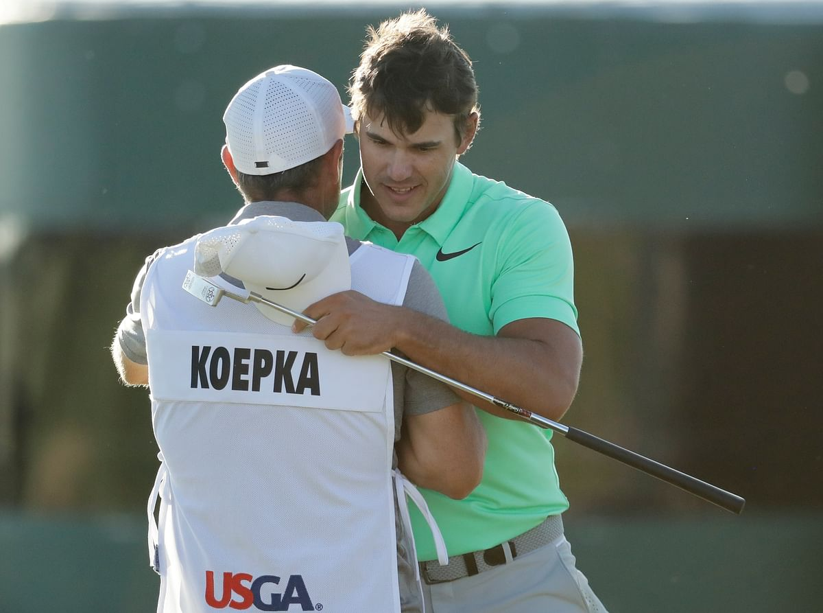 Brooks Koepka is congratulated by caddie Ricky Elliot after the fourth round of the U.S. Open golf.