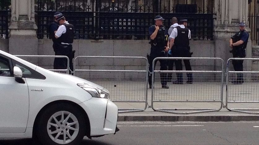 Police officers detain a man outside the Palace of Westminster, in central London. (Photo: Reuters)