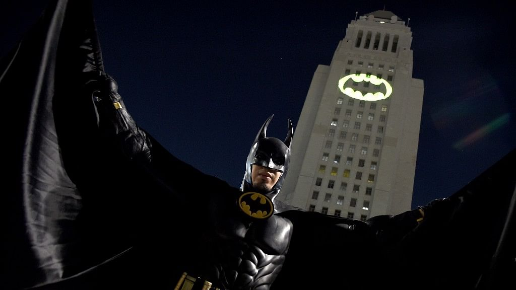 """A man poses in front of a Bat-Signal projected onto City Hall at a tribute to """"Batman"""" star Adam West on Thursday, June 15, 2017, in Los Angeles. (Photo: AP)"""