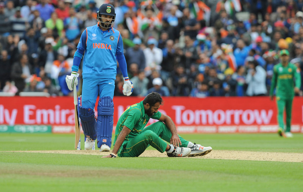 Pakistan's Wahab Riaz sits on the field holding his ankle after an injury during the ICC Champions Trophy match between India and Pakistan. (Photo: AP)