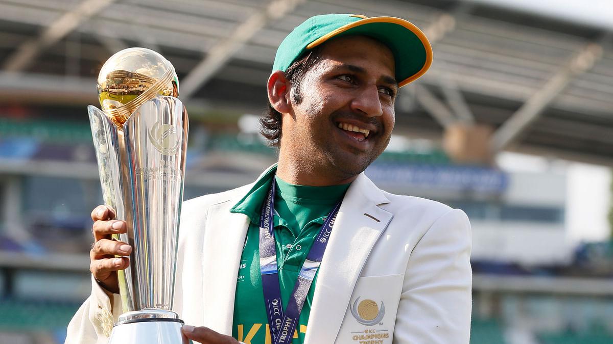 Pakistan's Sarfaraz Ahmed poses with the ICC Champions Trophy.