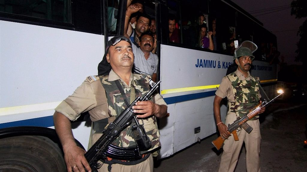 Security personnel stand guard near a bus with Amarnath pilgrims aboard.