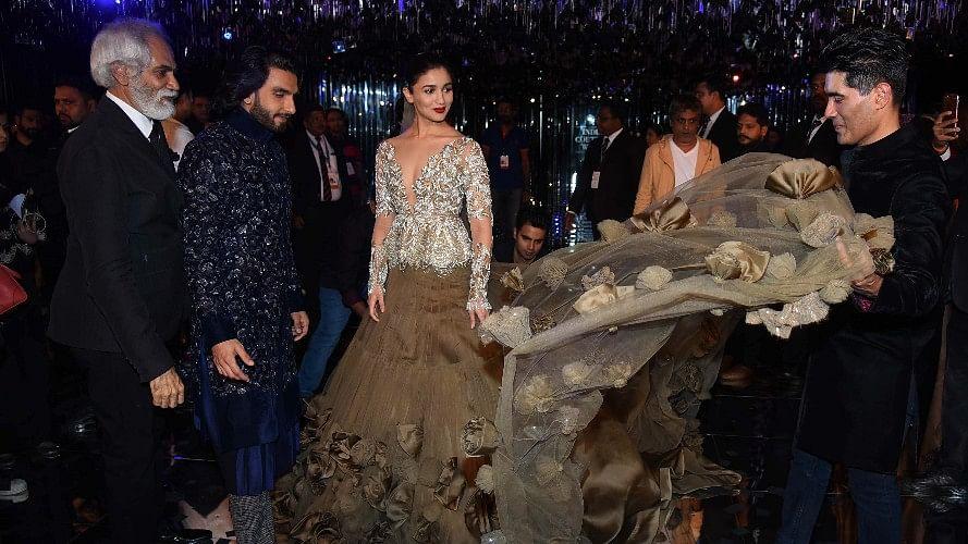 Manish Malhotra arranges Alia Bhatt's dress while Ranveer looks on.