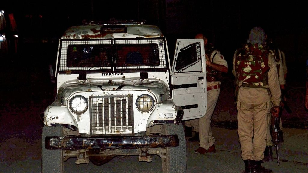 Security persons stand guard after militants opened fire on the Amarnath Yatra in which some pilgrims were killed in Anantnag in Jammu and Kashmir on Monday.